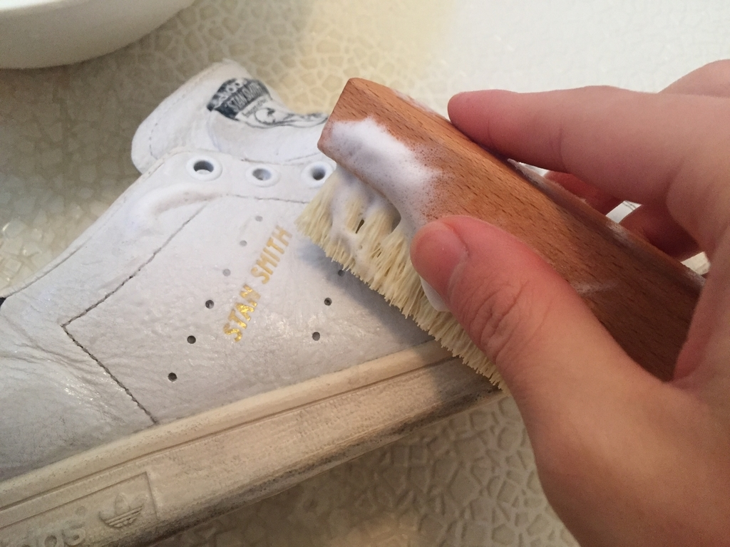 白スニーカーをブラシで磨いている画像